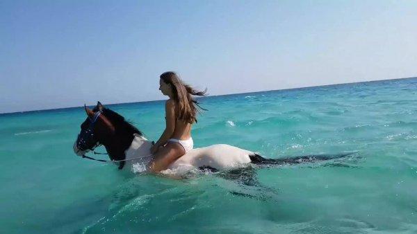 Mulher andando a cavalo em águas límpidas, confira que cenário incrível!