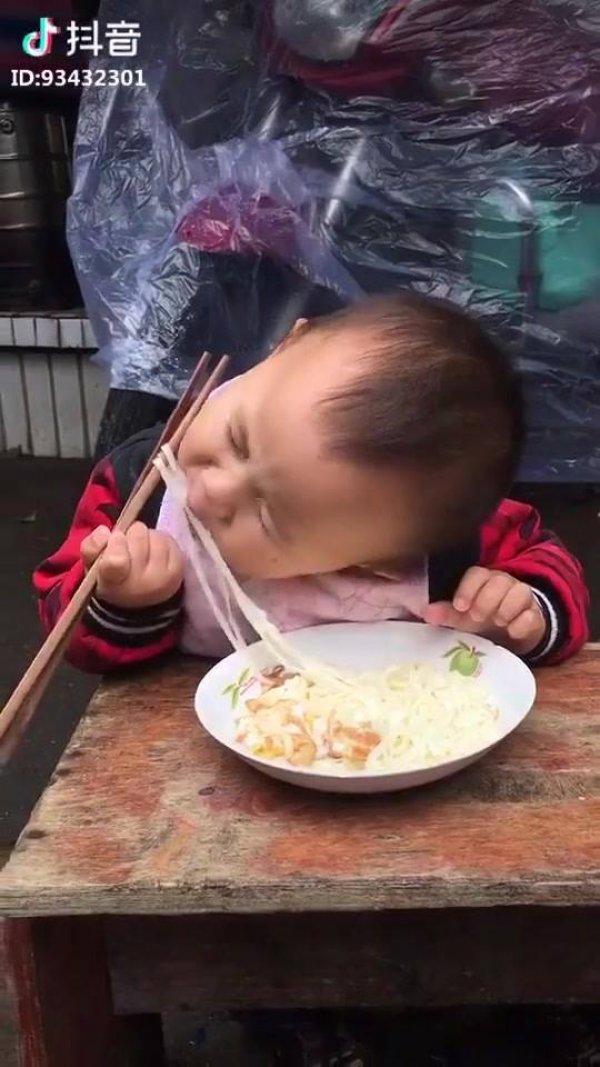 Criança comendo com palitos, ele é quase um bebê e já consegue!