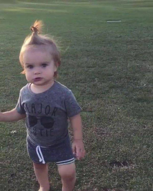 Criança andando pelo meio do campo e falando sozinha, que gracinha!