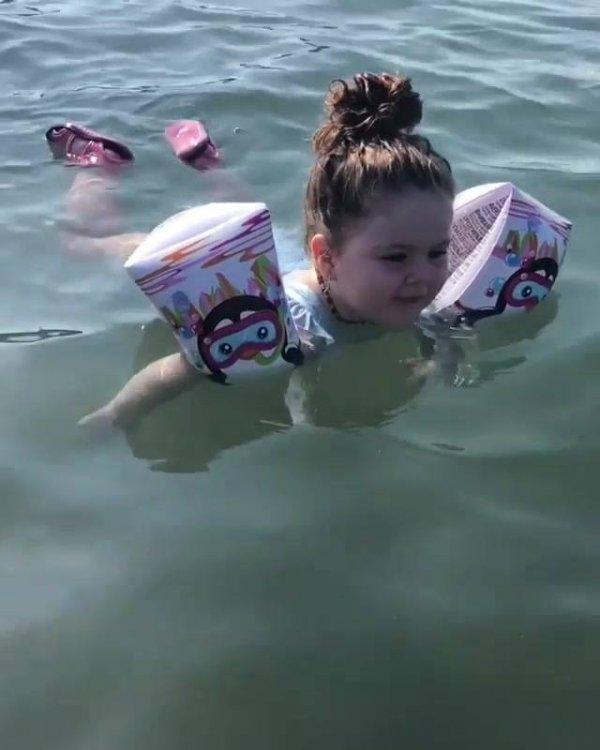 Criança nadando com boias no mar,que delicia de diversão, confira!