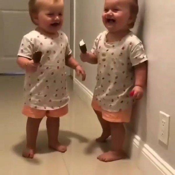 Gêmeas dando risadas com sorvete de palito na mão, que fofura!