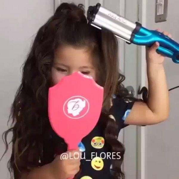 Garotinha enrolando os cabelos e passando batom, ela é muito linda!